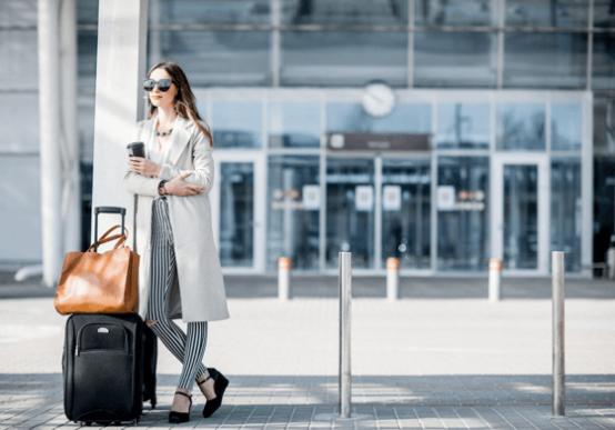Mujer joven con maletas esperando en el aeropuerto