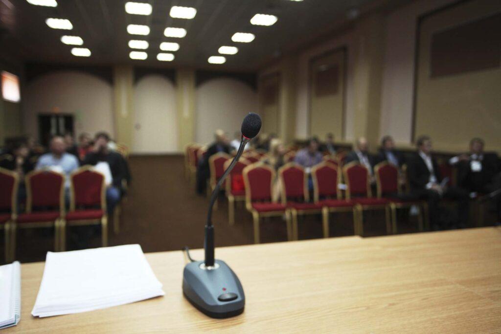 Micrófono con fondo de personas en una conferencia
